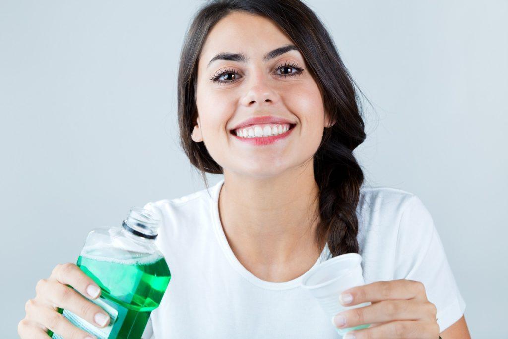 woman using mouthwash