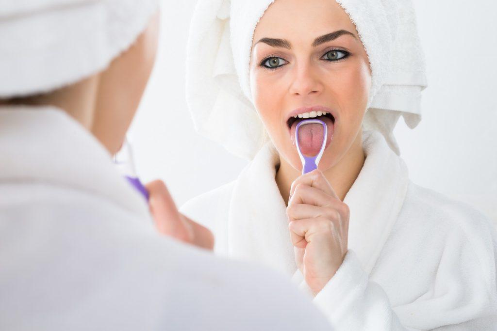woman scraping her tongue