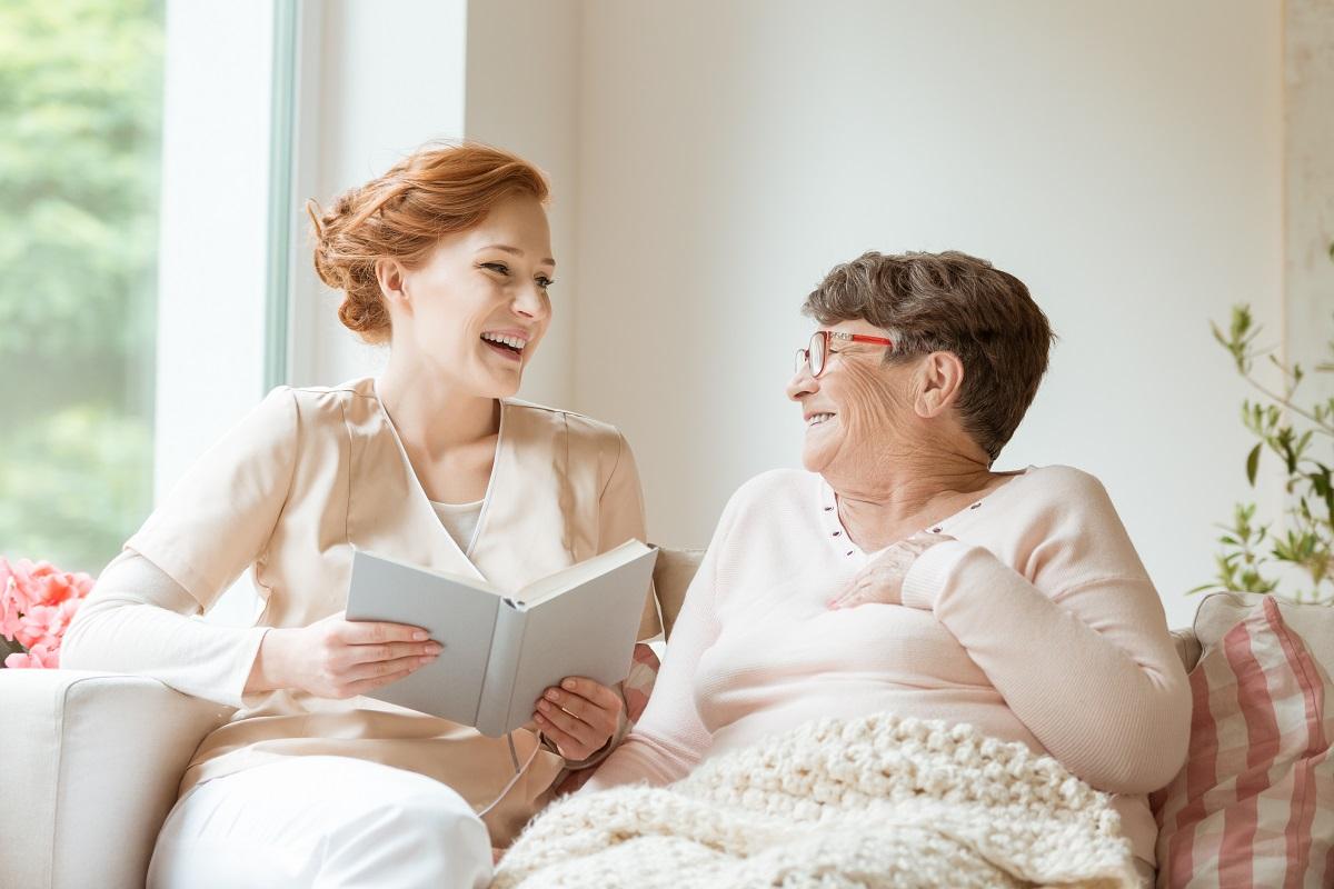 senior and caretaker laughing