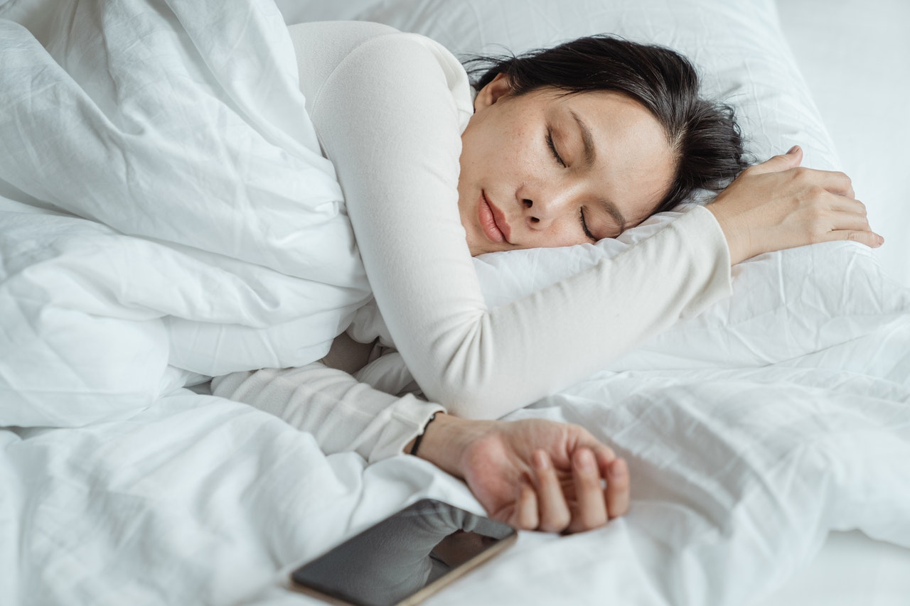 woman sleeping with phone on bed