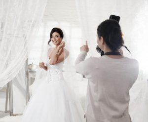 woman being photographed in wedding dress