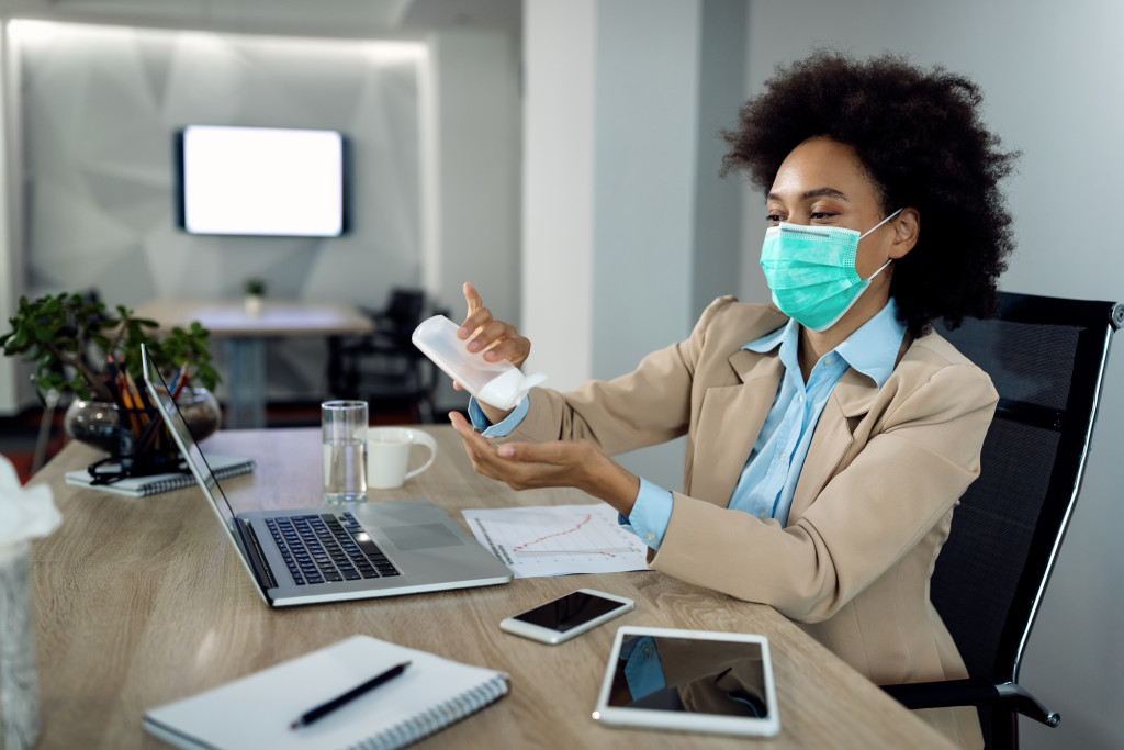 woman working with a facemask and applying sanitizer on her hands